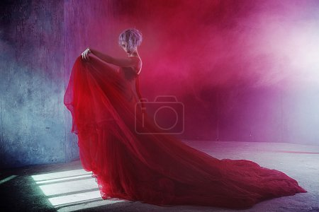 Fashion photo of young magnificent woman in red dress. Textured background, smoke