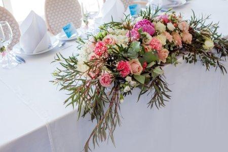 Photo pour Arrangement de fleurs sur la table. Fleurs sur une nappe blanche, roses et pivoines - image libre de droit
