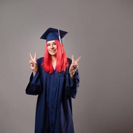 Photo pour Jeune femme est diplômée de l'université. Heureux maître diplômé en peignoir et casquette, heureux de recevoir un diplôme, portrait studio sur fond gris - image libre de droit