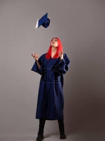 Photo pour Heureux diplômé sur fond gris. Une jeune femme aux cheveux brillants avec une casquette et une robe de chambre. Lance le capuchon. - image libre de droit