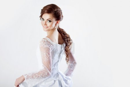 Portrait of happy bride in wedding dress, white background, space for text on the right