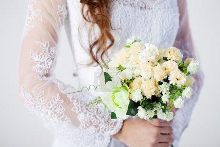Bridal bouquet. Bride in wedding dress, white background