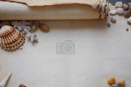 Photo pour Vieux parchemin de parchemin avec galets de mer et coquillages - image libre de droit