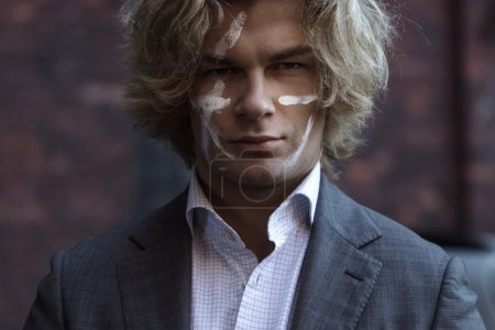 Businessman warrior. Young man makes war paint on his face, concept