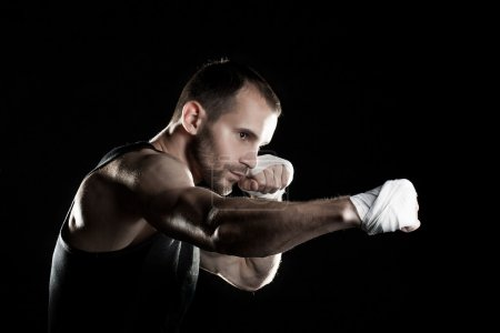 muscular man,strikes right, black background, horizontally