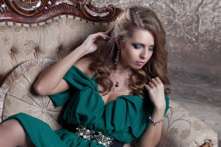 young attractive woman in green dress sits on a beautiful sofa