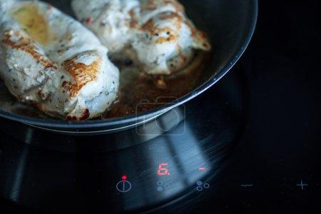 Kochen zu Hause, Hühnerfilet mit Tomate, Kochtopf, Induktionsherd