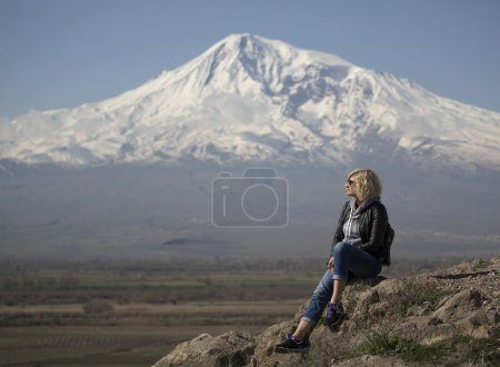 Beautiful blond woman with curly hair is looking into the distance near of the Ararat Mountain