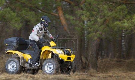 Photo pour Verticale horizontale de mouvement d'un homme dans le casque de sécurité et les lunettes conduisant le quad jaune 4x4 couvert de boue dans la veste grise de sport dans les bois. - image libre de droit