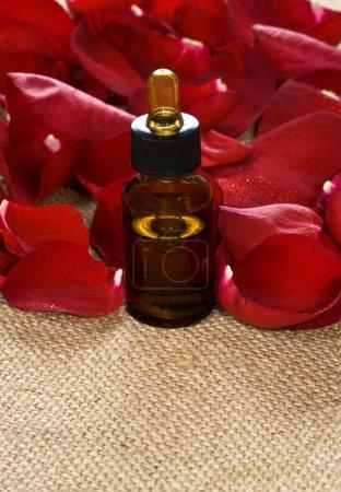 Photo pour Pétales de rose rouges et huile de massage sur un sac - image libre de droit