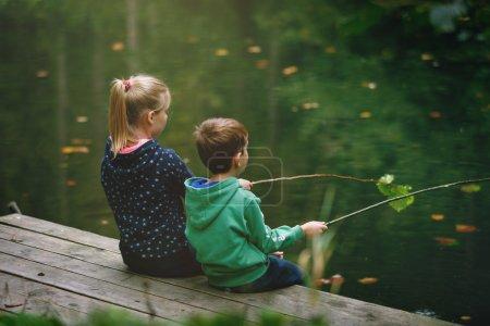 Photo pour Jeune fille et garçon jouant à l'extérieur imiter la pêche à un lac - image libre de droit
