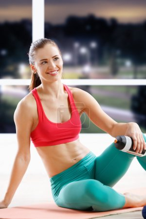 Photo for Portrait of happy athletic young woman resting after workout at fitness class in evening - Royalty Free Image