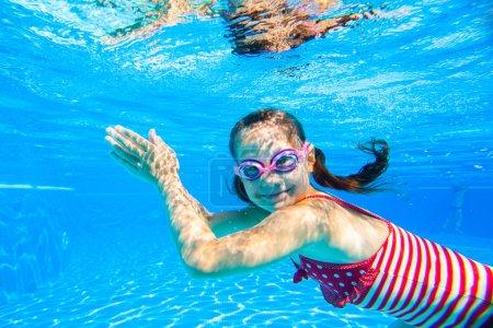 Photo pour Petite fille en maillot de bain rayé nageant dans la piscine sous l'eau - image libre de droit
