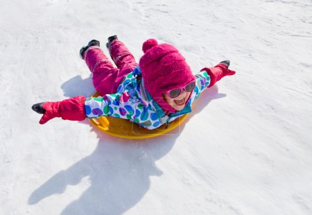 Photo for Little girl riding on snow slides in winter time - Royalty Free Image