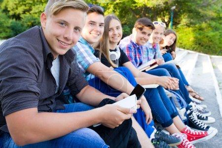 Photo pour Groupe de jeunes étudiants avec des livres et des gadgets assis sur les marches du parc - image libre de droit