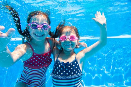 Two little girls underwater in pool