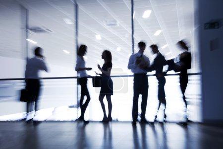 Photo pour Plusieurs silhouettes de gens d'affaires interagissant centre d'affaires arrière-plan - image libre de droit