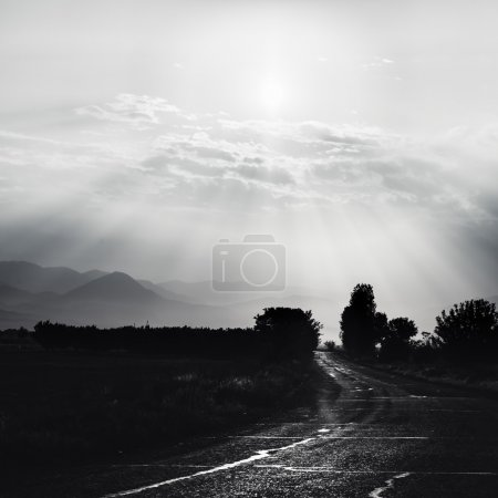 Monochrome road on meadow with beautiful sky