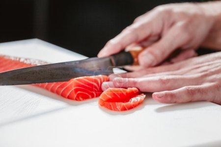 Cook cutting salmon