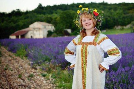 Photo pour Fille paysanne dans une couronne de fleurs vêtue d'une robe russe se dresse sur le chemin de terre le long du champ de lavande, ferme sur fond. Traitement croisé à partir du fichier RAW - image libre de droit