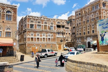 Photo for SANAA, YEMEN - MAR 6, 2010: Typical street scene in old city of Sanaa. Inhabited for more than 2.500 years at an altitude of 2.200 m, the Old City of Sanaa is a UNESCO World Heritage City now destroyed by the civil war - Royalty Free Image
