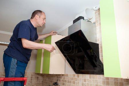Handwerker Küchen-Schreiner bei Küchenschrank-Montage serv