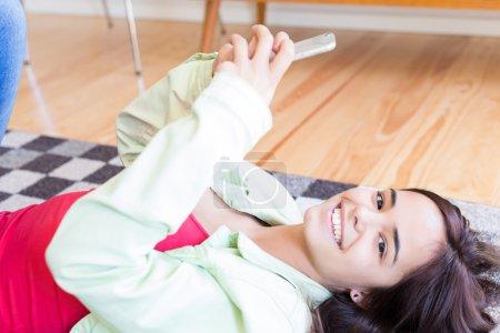 Photo pour Femme mise à jour de ses réseaux sociaux dans le téléphone portable tout en se relaxant dans le salon - image libre de droit