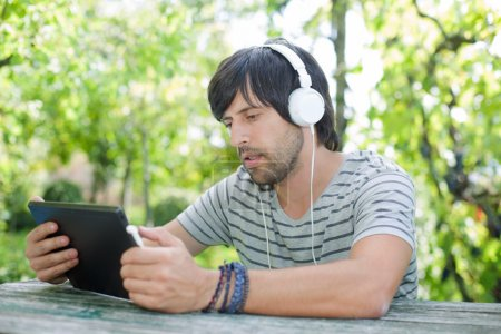 young man working with a tablet pc listening music with headphones