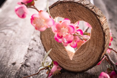 Heart hole in wood and flowers