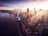 "Постер, картина, фотообои ""New York City - beautiful colorful sunset over manhattan fit sunbeams between buildings"""