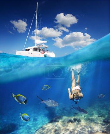 Photo pour Jeune fille, plongée dans l'océan avec des poissons à côté de catamaran à la journée ensoleillée - image libre de droit