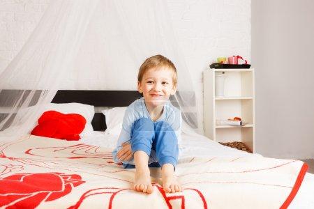 Photo pour Garçon souriant portant des confitures assis sur le lit des parents - image libre de droit