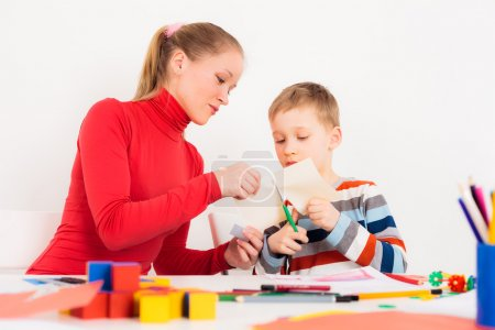 Mother helping her child to cut paper