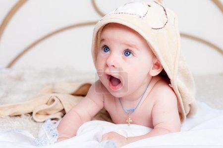 Kleines Baby lächelt unter Badetuch