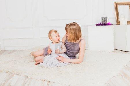 Photo pour Bébé fille et adolescent fille assis ensemble sur le sol dans la salle de lumière - image libre de droit