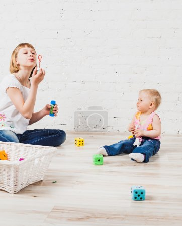Two sister sitting on floor and blowing bubbles