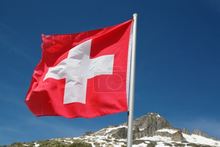Swiss flag over rocky cliffs