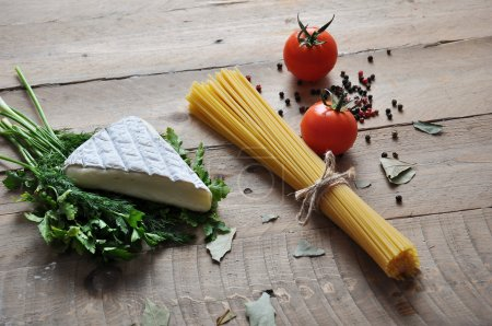 Photo for Brie cheese with herbs dill and parsley with different types of spaghetti noodles - Royalty Free Image