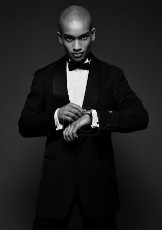 Studio fashion portrait of a handsome young African American businessman wearing a black suit and tie