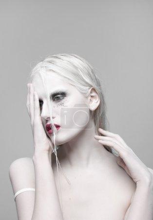 Haute Mode Beauté Modèle Fille avec maquillage sombre et longues poussées. Lèvres rouges. Rouge à lèvres foncé et peau blanche. Portrait de style Vogue