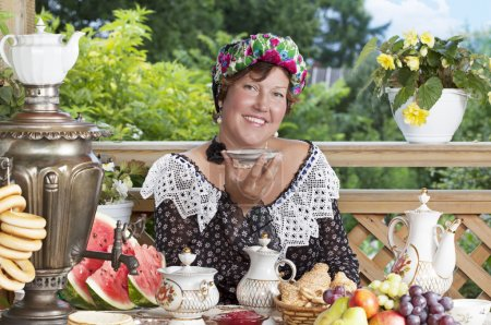 Joyful woman drinking tea outdoors