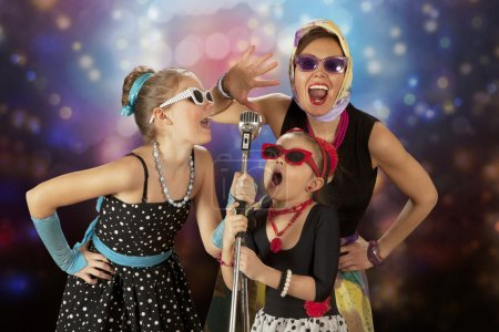 Photo for Rockabilly woman with her daughters having fun posing with vintage microphone in 1950s style clothing - Royalty Free Image