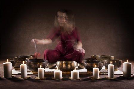 Woman playing Tibetan singing bowls