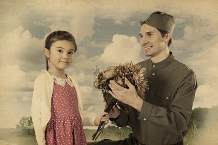 Маленькая девочка, вручающая букет цветов советских солдат