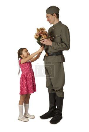 Маленькая девочка дает кучу цветов советских солдат