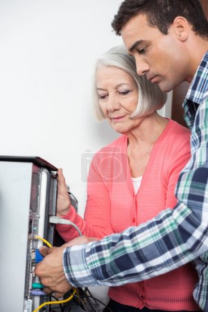 Tutor Assisting Senior Woman Setting Up Computer