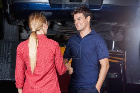 Smiling Mechanic Shaking Hand With Customer