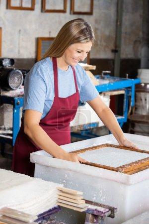 Photo pour Moule de trempage ouvrière heureuse dans le mélange de pâte et d'eau à l'usine de papier - image libre de droit