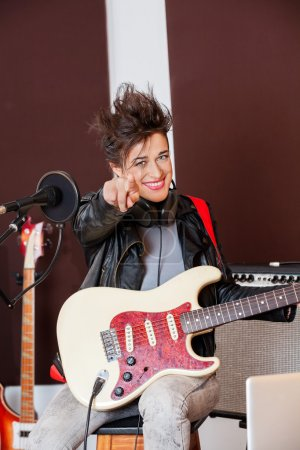 Female Guitarist Pointing While Performing In Studio