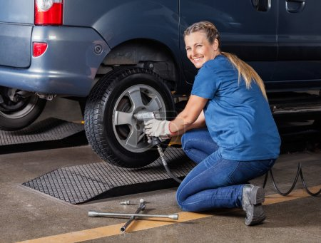 Happy Female Mechanic Fixing Tire With Pneumatic Wrench